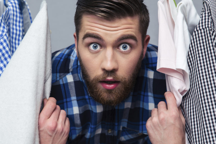 Portrait of a surprised hipster man standind near rack with clothes and looking at camera
